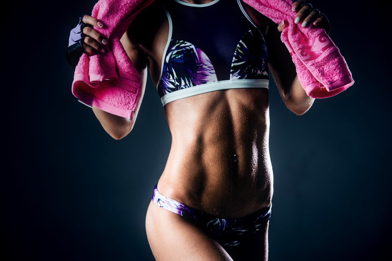 Fit woman posing with a pink towel on dark background